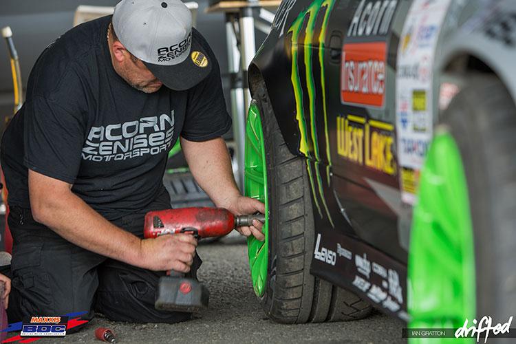 man changing wheels on drift car